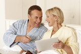 Couple in bed using digital tablet together
