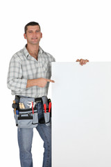 Handyman pointing at blank poster