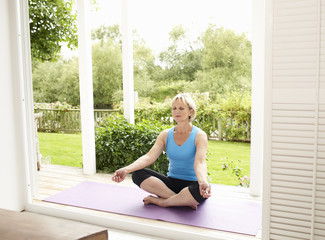 Woman practicing yoga on porch