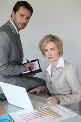 businessman and woman at desk