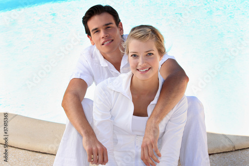 Portrait of a young couple sitting at the poolside