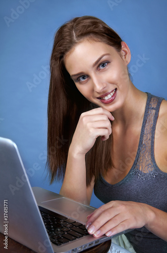 Pretty girl in trade fair with laptop smiling