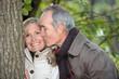 Older man kissing his partner under a tree