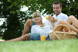 couple drinking orange juice in a park