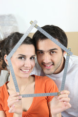 Couple holding house-shaped measuring device