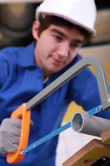 young man is cutting a pvc pipe with a saw