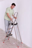 Man painting on a ladder
