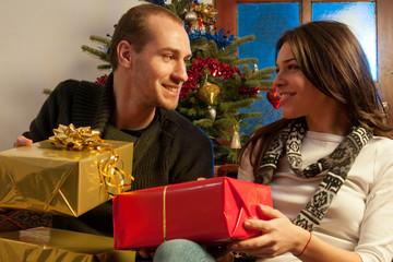 beautiful couple admiring christmas gifts