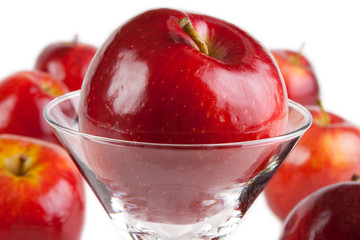 Red apples, one  in drink glass, white background