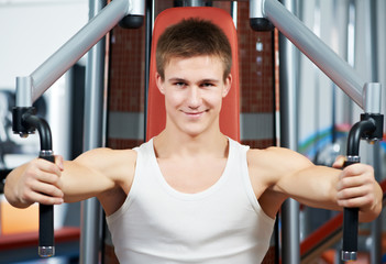positive man at chest exercises machine