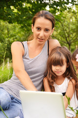 Mother and daughters using laptop outdoor.