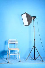 Studio flash with softbox and old chair over the blue background