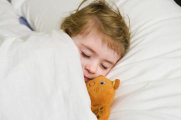 Bambina che dorme con orsetto