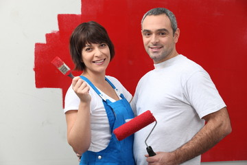 Couple painting a room red