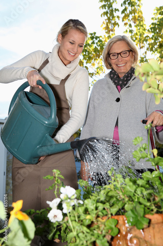 Young woman spending time with her grandmother in the garden