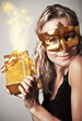 Stylish woman with golden mask and gift
