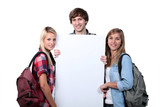 Teenagers holding up a blank poster