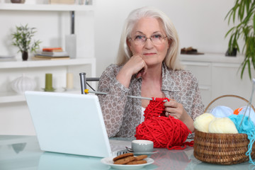 Elderly woman knitting by her laptop
