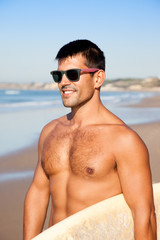 Handsome muscular surfer with surf board