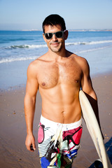 Muscular surfer with surf board