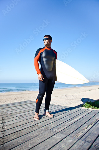 Surfer with surf board wearing a wetsuit