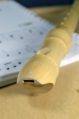 A wooden recorder on sheet music. Selective focus