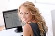 Portrait of beautiful woman sitting in front of desktop computer