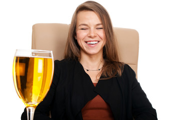 Businesswoman in leather chair with glass of cider laughing