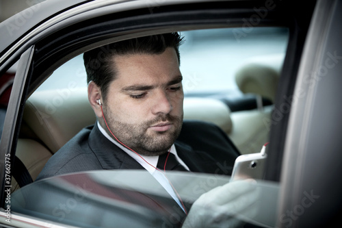 Businessman  listening to music on his phone