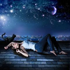 Mädchen auf Dach liegend unter wunderschönem Sternenhimmel / h