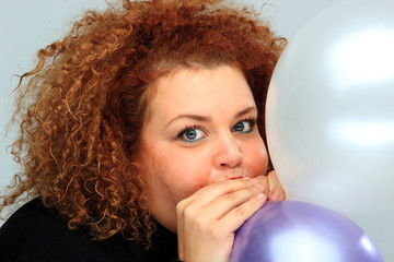 young woman in black shirt inflating balloon