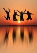 silhouette of girls jumping in sunset at beach