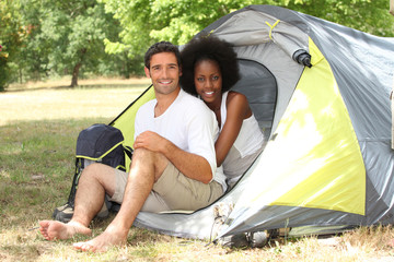 Happy couple sat by entrance to tent
