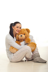 Woman in pyjama hugging bear