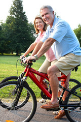Senior couple cycling in park.