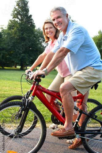 Plexiglas Wielersport Senior couple cycling in park.