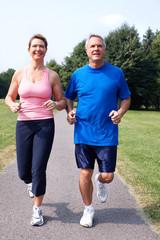 Senior couple jogging in park.