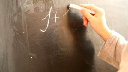 child writes on the chalk board