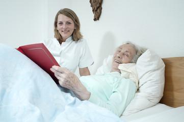 Seniorin und Pflegerin schauen durch ein fotoalbum