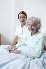 Pflegerin und Seniorin lachen in die Kamera
