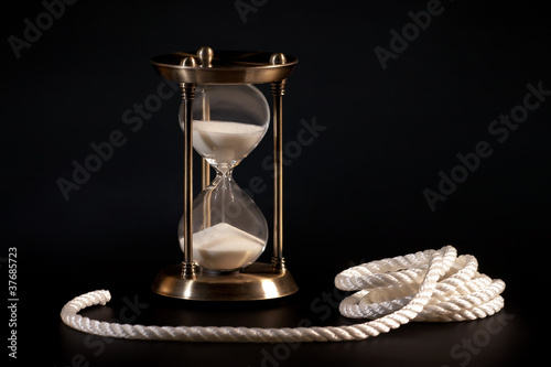 Sand clock and rope on black background