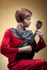 Woman in renaissance costume playing mandolin