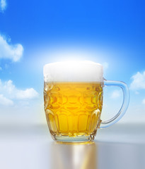 Cold beer in glass on blue sky background