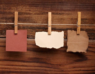 grunge note paper and clothes peg on wood