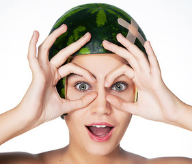 Fancy young girl with watermelon as a helmet on her head