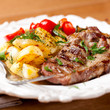 Grilled pork steak with roasted potatoes and herbs