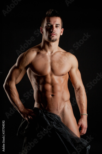 Muscular young sexy naked man wrapped in silk
