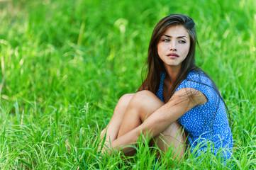 sad woman sitting on grass