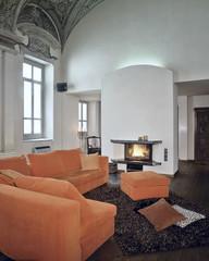 divano arancione davanti al camino acceso in casa moderna
