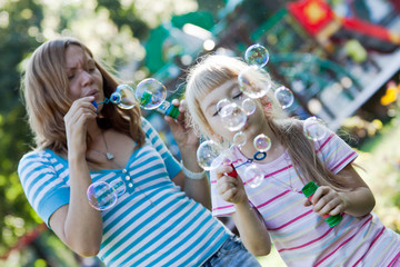 Two sisters having fun, making water bubbles.